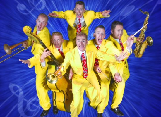 The Jive Aces posing with their instruments wearing their famous canary yellow zoot suits in front of a blue background emblazoned with musical notations