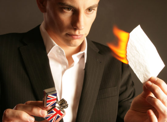 Close up magician Matt burning a piece of paper as part of a magic trick