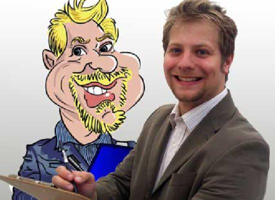 Caricaturist David With a Clip Board in Hand Stands in Front of a Self Portrait Drawn in a Cartoon Style