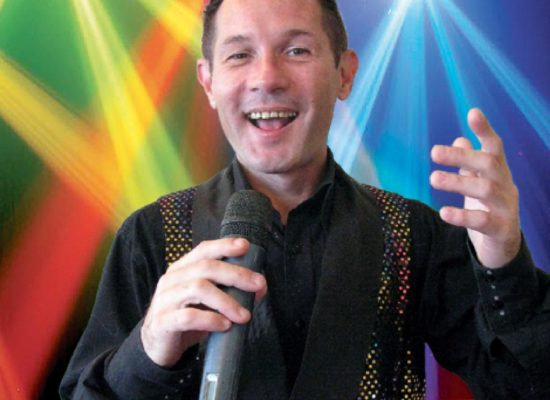 Gary Richard Cabaret Performer Mid Song Against A Disco Coloured Lighting Background