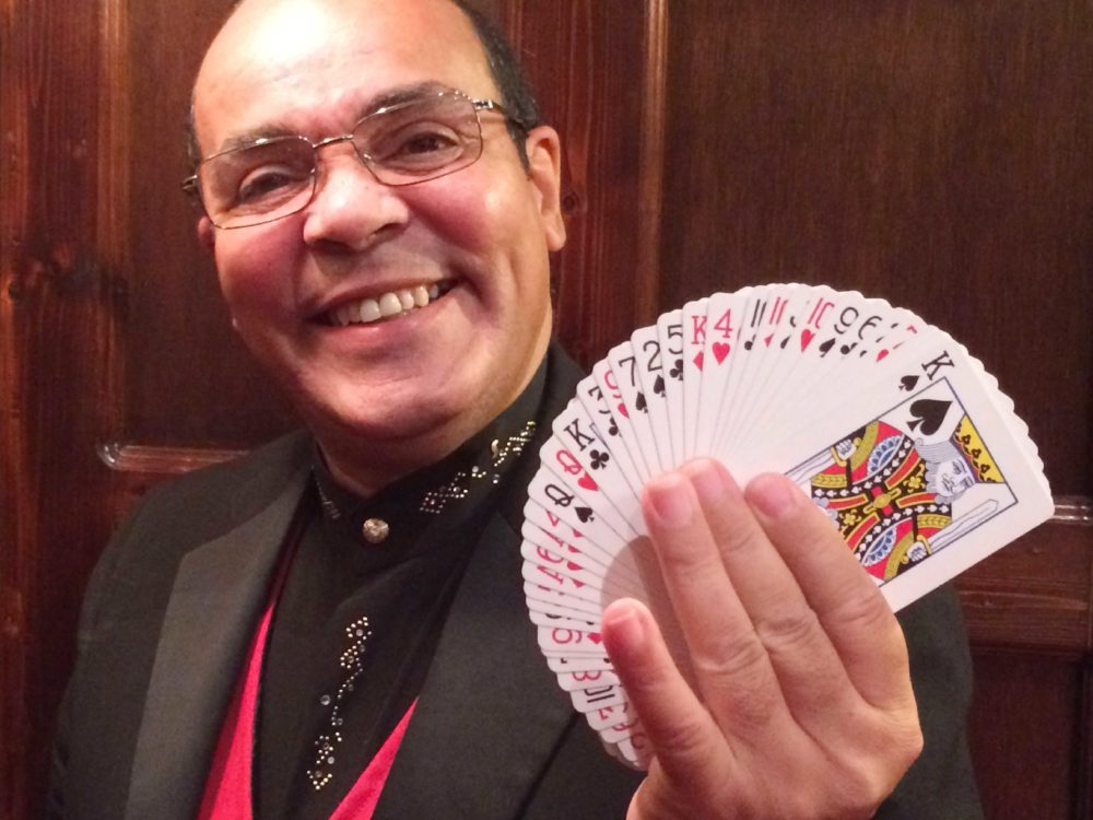 Close Up Magician Jay Smiling and Holding a Fan of Playing Cards