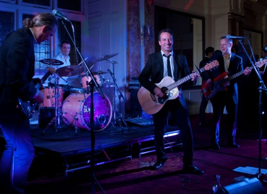 The Dukes Corporate Party Band Playing Live at a Corporate Event Bathed in Blue Light
