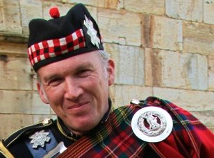 Bagpipe Player John In Full Regalia Against The Stone Wall Of A Wedding Venue
