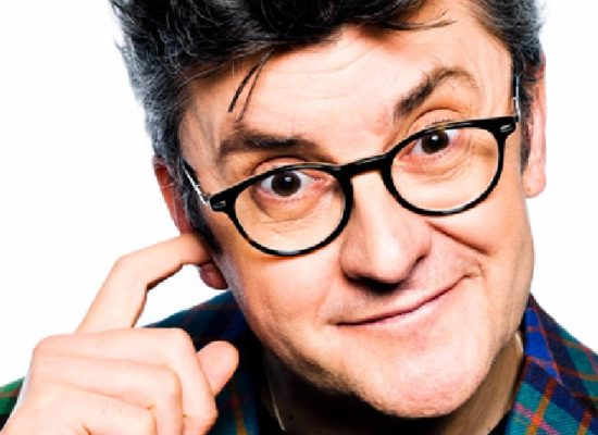 Joe Pasquale Comedian Wearing A Vibrant Tartan Jacket Against A White Background