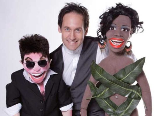 Steve Hewlett Ventriloquist With Sinitta & Simon Cowell Puppets Against A White Background