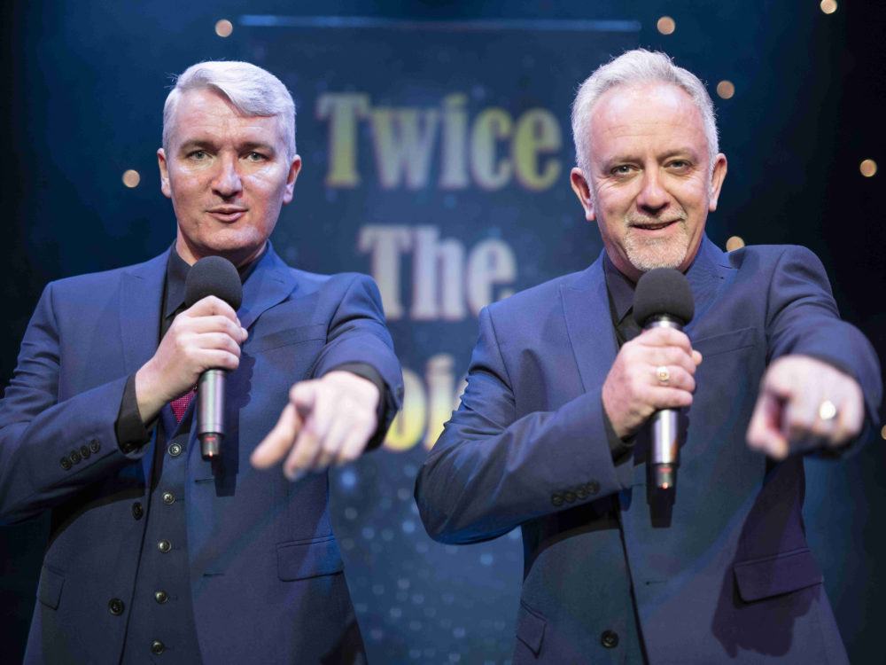 Twice The Voice Retro Party Duo Pointing To Audience In Front Of A Twice The Voice Backdrop