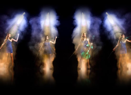 Siren Electric Violin Quartet In Haze Spotlights Against A Black Background