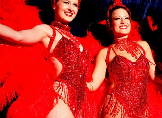 Vegas Showgirls In Red Feathered Costumes Performing On Stage