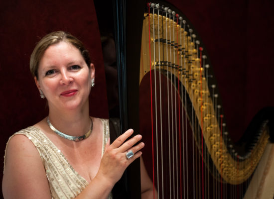 Fiona Harpist In White Gown Against A Black Background